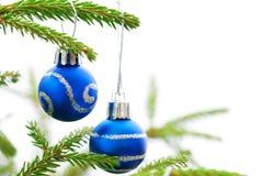 Julgranträd med två blåa julbollar Fotografering för Bildbyråer