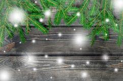 Julgranträd på träbakgrund med snöflingor Royaltyfria Foton