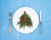 Julgranträd som göras av arugula och körsbärsröda tomater på vit Royaltyfri Bild