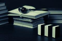 Julgue o martelo ao lado da pilha dos livros no fundo de madeira Foto de Stock