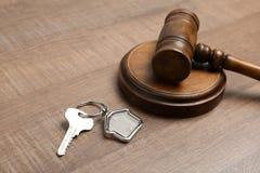 Julgue o martelo e abrigue a chave no fundo de madeira, close up Conceito da lei da propriedade imagens de stock royalty free