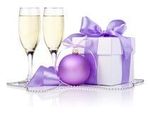Julgåva, purpur boll, två champagneexponeringsglas Arkivbilder