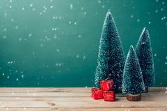 Julgåvaaskar sörjer under trädet på trätabellen över grön bakgrund Royaltyfria Foton