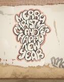 Julhälsningar, sprej som målas, på den gamla väggen. Arkivbild