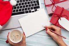 Julhälsningkort, gåvaaskar, PC och kaffekopp på trä Royaltyfria Bilder