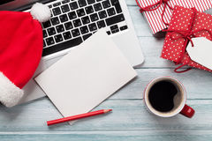 Julhälsningkort, gåvaaskar, PC och kaffekopp på trä Royaltyfri Bild