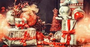 Julhälsningkort med gåvaaskar med bandet, garneringbollen och fågeln på festlig bokehbelysningbakgrund som är horisontal Arkivbilder