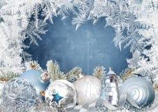 Julhälsningkort med härliga bollar på en blå snöig bakgrund med frostiga modeller stock illustrationer