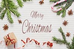 Julhälsningkort med text Gåvaask med bandet, granfilialer, stjärnaanis och godisen på stucken vit bakgrund fotografering för bildbyråer