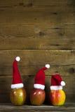 Julhälsningkort med tre röda santa hattar på äpplen med Arkivbilder