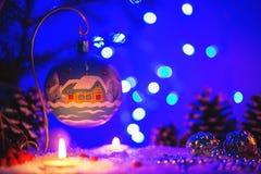 Julhälsningkort med xmas-leksaken och vinterlandskap på det royaltyfria foton