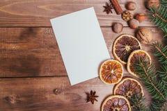 Julhälsningkort och matdekor på trätabellen med granträdet Bästa sikt med kopieringsutrymme Arkivfoto