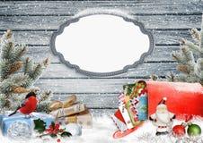 Julhälsningkortet med ramen, gåvor, en brevlåda med bokstäver, sörjer filialer och julgarneringar Royaltyfri Foto
