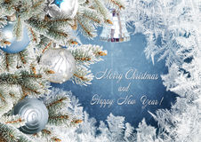 Julhälsningkortet med sörjer filialer och bollar på den frostiga modellbakgrunden Arkivfoto