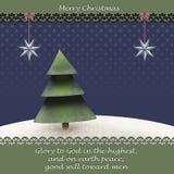 Julhälsningkortet med winterlandscape för julträd I och en bibel citerar från Luke 2 14 arkivfoton