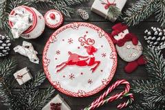 Julhälsningkortet på wood bakgrund, gran förgrena sig, kottar, snögubbe arkivbilder