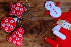 Julhantverk som ska göras hemma Filtstjärna, julgran, snögubbe och boll på en brun träbakgrund med kopieringsutrymme Arkivbilder