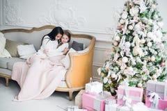 julhelgdagsaftongåvor semestrar många prydnadar familjmoder och läs- magisk bok för barndotter hemma på en soffa nära julgranen arkivbilder