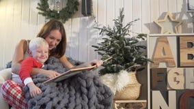 julhelgdagsaftongåvor semestrar många prydnadar Mamman läser en bok till hennes son Hon vänder sidorna lager videofilmer