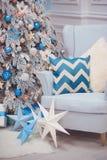 Julhemmiljö - en hemtrevlig fåtölj och en dekorerad gran i blåa vita färger nytt år Royaltyfri Bild