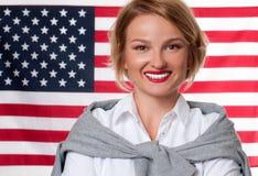 ô julho Jovem mulher de sorriso no fundo da bandeira do Estados Unidos Foto de Stock Royalty Free
