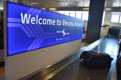 2016 julho Verona Italy - a boa vinda do ` do quadro indicador ao ` de Verona Airport no aeroporto e a bagagem alinham Imagem de Stock Royalty Free