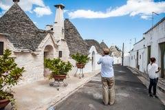 Juli 10, 2014 alberobello italy Turister fotograferas mot sikten Puglia Italien på en solig dag Trulli fotografering för bildbyråer
