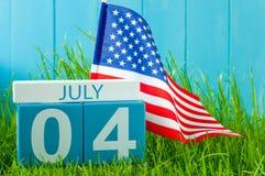 4 juli Beeld van 4 juli houten kleurenkalender op blauwe achtergrond met vlag van de V.S. Boom op gebied Onafhankelijkheidsdag va Stock Foto