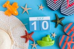10 juli Beeld van 10 juli kalender met de toebehoren van het de zomerstrand en reizigersuitrusting op achtergrond Boom op gebied Royalty-vrije Stock Afbeelding
