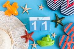 11 juli Beeld van 11 juli kalender met de toebehoren van het de zomerstrand en reizigersuitrusting op achtergrond Boom op gebied Royalty-vrije Stock Afbeeldingen