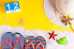 12 juli Beeld van 12 juli kalender met de toebehoren van het de zomerstrand en reizigersuitrusting op achtergrond Boom op gebied Stock Foto