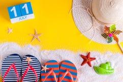 11 juli Beeld van 11 juli kalender met de toebehoren van het de zomerstrand en reizigersuitrusting op achtergrond Boom op gebied Royalty-vrije Stock Afbeelding