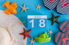 18 juli Beeld van 18 juli kalender met de toebehoren van het de zomerstrand en reizigersuitrusting op achtergrond Boom op gebied Stock Foto