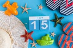 15 juli Beeld van 15 juli kalender met de toebehoren van het de zomerstrand en reizigersuitrusting op achtergrond Boom op gebied Stock Fotografie