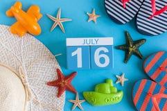 16 juli Beeld van 16 juli kalender met de toebehoren van het de zomerstrand en reizigersuitrusting op achtergrond Boom op gebied Stock Fotografie