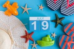19 juli Beeld van 19 juli kalender met de toebehoren van het de zomerstrand en reizigersuitrusting op achtergrond Boom op gebied Royalty-vrije Stock Afbeeldingen