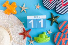 11. Juli Bild des vom 11. Juli Kalenders mit Sommerstrandzubehör und Reisendausstattung auf Hintergrund Baum auf dem Gebiet Lizenzfreie Stockbilder