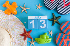 13. Juli Bild des vom 13. Juli Kalenders mit Sommerstrandzubehör und Reisendausstattung auf Hintergrund Baum auf dem Gebiet Stockbilder