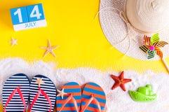 14. Juli Bild des vom 14. Juli Kalenders mit Sommerstrandzubehör und Reisendausstattung auf Hintergrund Baum auf dem Gebiet Lizenzfreie Stockbilder