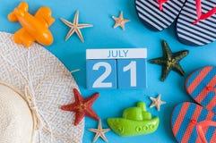 21. Juli Bild des vom 21. Juli Kalenders mit Sommerstrandzubehör und Reisendausstattung auf Hintergrund Baum auf dem Gebiet Lizenzfreie Stockfotos
