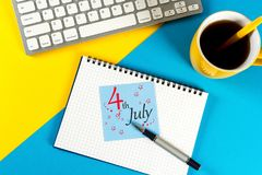 4. Juli Bild des vom 4. Juli Kalenders auf Büroarbeitsschreibtisch mit MorgenKaffeetassehintergrund Baum auf dem Gebiet Unabhängi Stockfoto