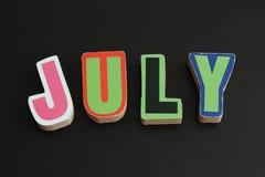 Juli-Buchstaben auf schwarzem Hintergrund Lizenzfreie Stockfotos