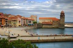 17 JULI 2009, COLLIOURE, FRANKRIKE - turister tycker om att besöka Notren Dame Church som förbiser hamnen av Collioure Arkivfoto