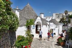 Juli 2013: Das Schattenbild von ein touristischen Erforschungstrulli-Häusern in Alberobello Stockbild