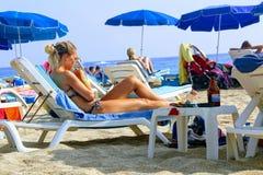 Juli, 2017 - de Mensen rusten op deckchairs in de schaduw van strandparaplu's op Cleopatra Beach Alanya, Turkije Stock Afbeelding