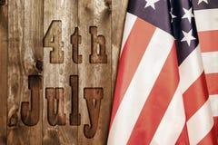 Juli 4., der US-Unabhängigkeitstag, Platz zu annoncieren, hölzerner Hintergrund, amerikanische Flagge Lizenzfreies Stockbild