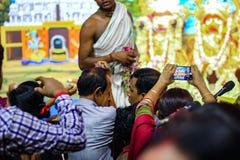 Juli 2018, Durgapur, West-Bengalen, India Een Purohit Panda Blessing een liefhebber met heilige bloemen bij het Festival van Rath stock foto