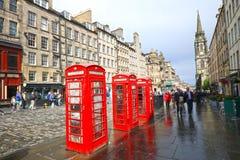 1 juli, 2017 Edinburgh, het UK: Iconische rode Britse Telefooncel bij de Toeristendistrict van Edinburgh, toeristen die langs lop Stock Afbeelding
