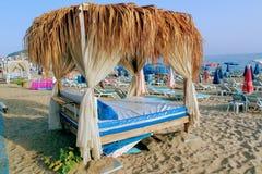 Juli 2017 - eine Überdachung von Palmblättern über den Tabellen eines Strandcafés in Alanya, die Türkei lizenzfreie stockfotografie