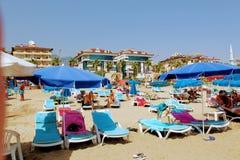 Juli 2017 - folket vilar på deckchairs i skuggan av strandparaplyer på Cleopatra Beach Alanya, Turkiet Royaltyfri Fotografi